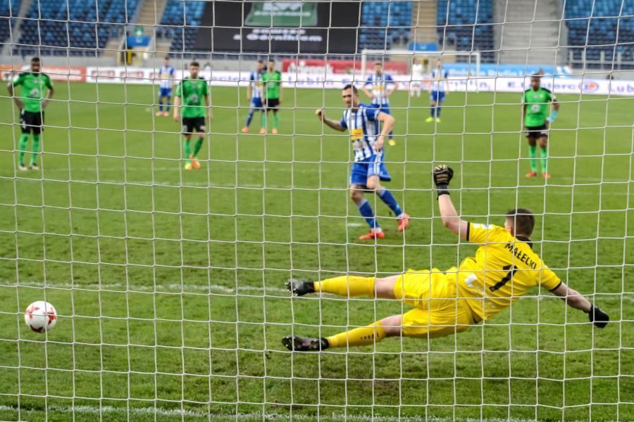 Piłkarz Wisły Płock Piotr Wlazło (C) pokonuje z rzutu karnego Wojciecha Małeckiego (#1) z Górnika Łęczna