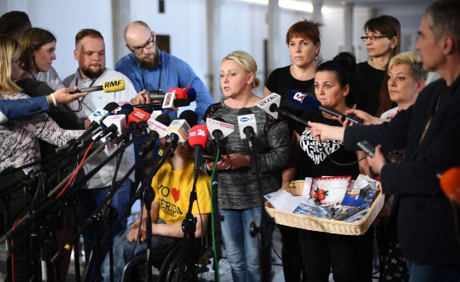 Iwona Hartwich (C) oraz niepełnosprawni i ich opiekunowie podczas konferencji prasowej w Sejmie