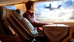 Mężczyzna w pociągu obserwujący samolot