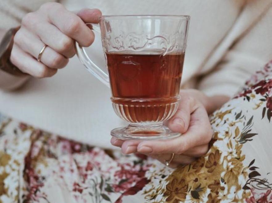 Kobieta trzyma szklankę z herbatą