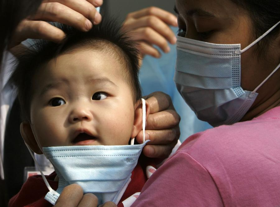 Maluch osłaniany maską tuż przed przyjęciem do szpitala w Hong Konkgu w 2008 roku. Z powodu epidemii grypy zamknięto wówczas szkoły i przedszkola