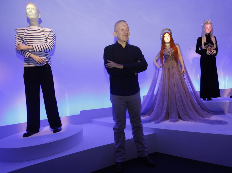"Jean Paul Gaultier na tle wystawy swoich projektów zatytuowanej ""The Fashion World of Jean Paul Gaultier"""