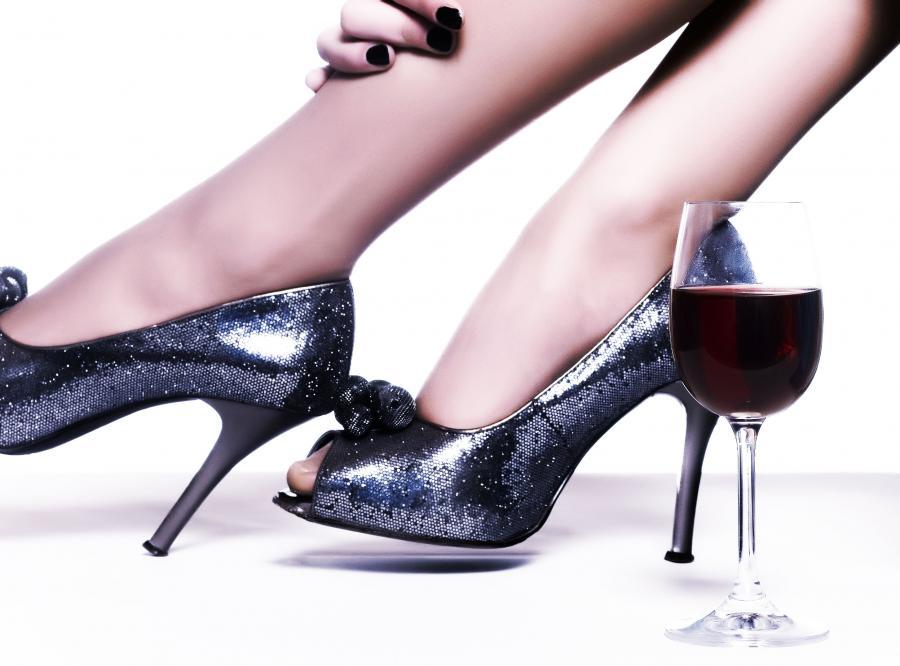 Kobiece szpilki i kieliszek z winem