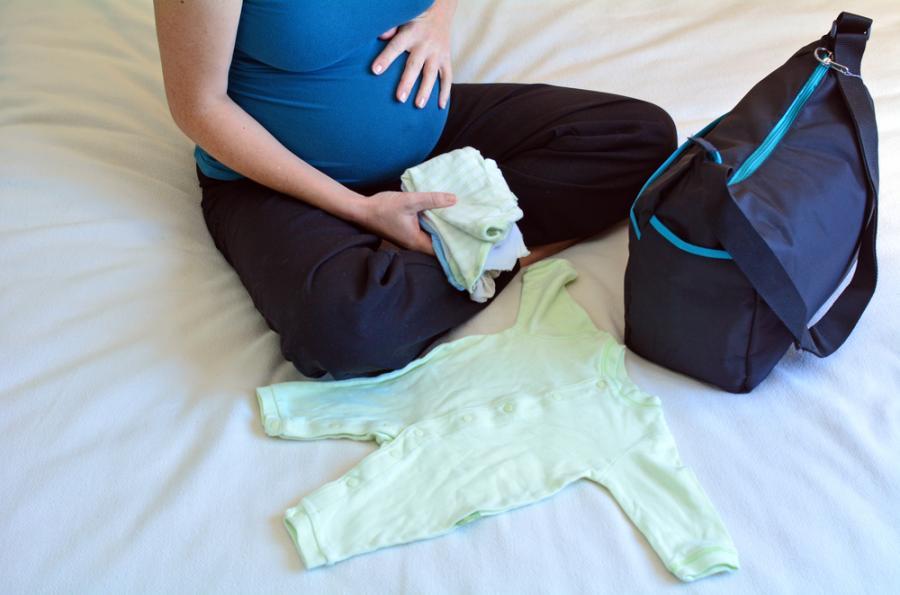 Kobieta w ciąży pakująca torbę do szpitala