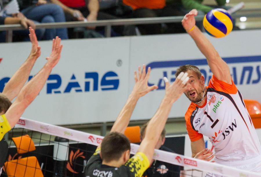 Piłkę zbija atakujący po drugiej stronie siatki Michał Łasko (P) z Jastrzębskiego Węgla nad blokiem Wojciecha Grzyba (C) Lotosu Trefl Gdańsk