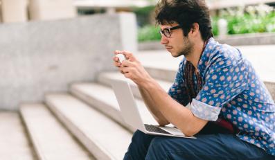 Mężczyzna ze smartfonem i laptopem