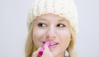 Kobieta nakłada pomadkę na usta