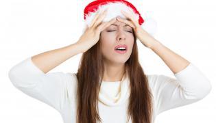 Kobieta w czapce Mikołaja trzyma się za głowę