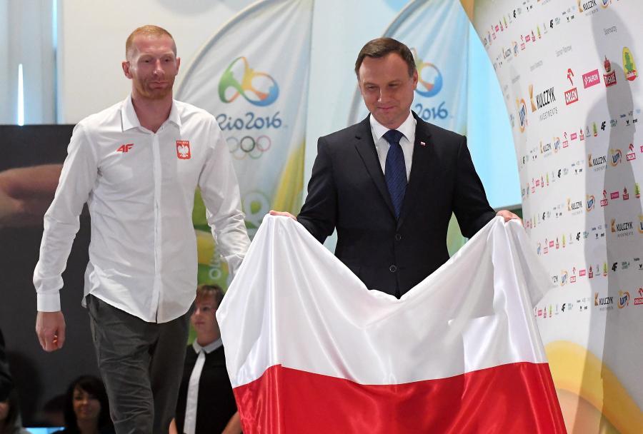 Chorąży reprezentacji Polski Karol Bielecki (L) i prezydent Andrzej Duda (P) podczas uroczystości wręczania nominacji i składania ślubowań przez członków reprezentacji Polski na Igrzyska w Rio de Janeiro